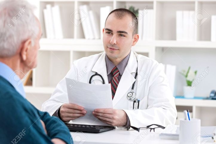 19404863-male-doctor-talking-with-senior-patient-at-office-stock-photo